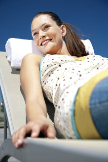 Smiling young woman relaxing in deckchair - TOYF001339