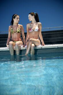 Two happy young women sitting at the poolside - TOYF001341
