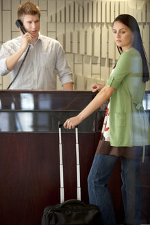 Woman standing at hotel reception with rolling suitcase - TOYF001348