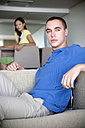 Young man sitting on couch with woman in background - TOYF001388