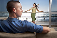 Young man on couch with girlfriend standing on balcony by the sea - TOYF001390