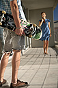 Young man with skateboard on balcony and woman in background - TOYF001357