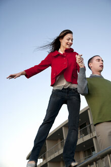 Young man supporting girlfriend balancing on railing - TOYF001409