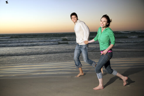 Young couple running hand in hand on the beach at dusk - TOYF001370
