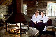 Smiling senior couple wearing bathrobes sitting at the fireplace - TOYF001284