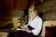 Smiling senior man sitting on bench in bathrobe reading a book - TOYF001290