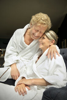 Happy senior couple in bathrobes hugging in armchair - TOYF001305