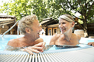 Happy senior couple in swimming pool at a spa - TOYF001311
