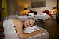Senior woman lying on massage table with closed eyes - TOYF001317