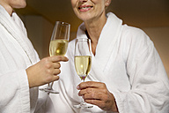 Two women in bathrobes clinking champagne glasses - TOYF001320