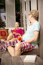 Smiling senior couple sitting on lounge outdoors with cocktails - TOYF001323