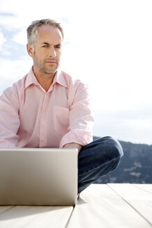 Portrait of serious looking man with laptop - TOYF001172