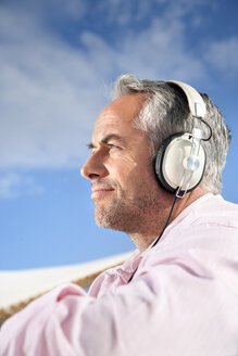 Portrait of mature man with stubble hearing music with headphones - TOYF001174