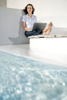 Spain, Mallorca, portrait of smiling woman sitting with laptop besides swimming pool - TOYF001177