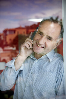 Portrait of smiling man telephoning while looking through the window - TOYF001193