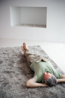 Mature man lying relaxing on a carpet at home - TOYF001203