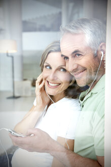 Portrait of smiling couple with earphones and mp3 player looking through window - TOYF001209