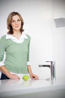 Portrait of woman standing in a modern kitchen - TOYF001210