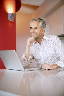 Portrait of smiling man with laptop looking at distance - TOYF001229