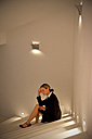 Overstressed businesswoman sitting on stairs - TOYF001220