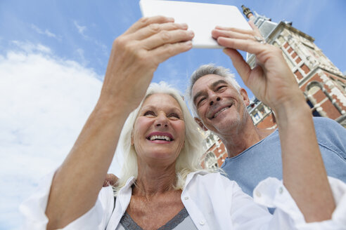 Netherlands, Amsterdam, senior couple taking a selfie in front of central station - FMKF002051
