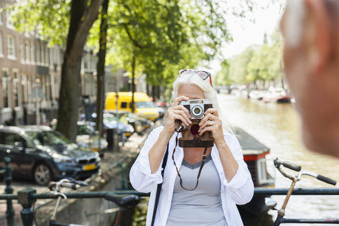 Netherlands, Amsterdam, senior woman taking a picture with analog camera at town canal - FMKF002015
