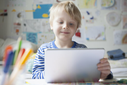 Portrait of smiling little boy using digital tablet - RBF002994