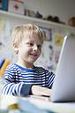 Portrait of smiling little boy using laptop - RBF002991