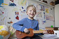 Portrait of smiling little boy sitting on his bed of his room playing guitar - RBF003000