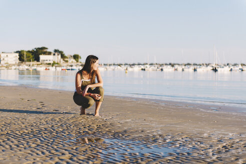 France, Pornichet, woman crouching on the beach at sunset - GEMF000337