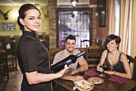 Waitress in bar ready to serve wine to a couple - JASF000028