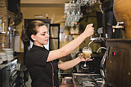 Waitress tapping beer in pub - JASF000032