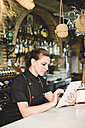 Waitress in bar with digital tablet looking at orders - JASF000036