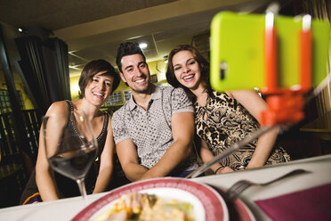 Three happy friends in a restaurant taking a selfie - JASF000039
