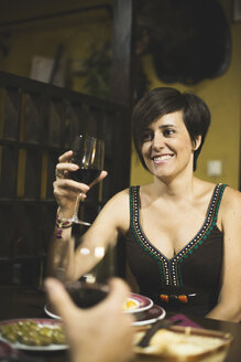 Smiling woman holding red wine glass in a traditional Spanish bar - JASF000041