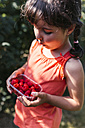Little girl with plastic box of raspberries - MGOF000575