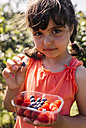 Portrait of little girl with plastic box of raspberries and blueberries - MGOF000577