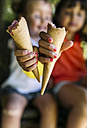 Hands of two little girls holding ice cream cones - MGOF000584
