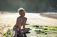 Portrait of a blond little girl sitting on a rock on the beach - MGOF000588