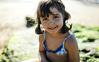 Portrait of smiling little girl on the beach - MGOF000593