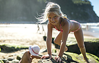 Portrait of little girl climbing on a rock at the beach - MGOF000661