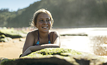 Portrait of smiling girl leaning on a rock at the beach - MGOF000600