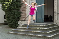 Portrait of happy blond woman jumping in the air after leaving the church - FRF000321