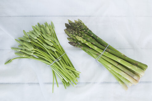 Two bunches of green and wild asparagus on white cloth - ASF005678