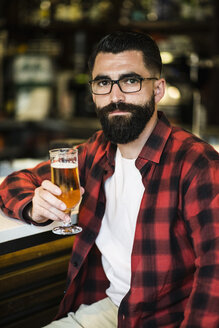 Portrait of hipster sitting in a bar holding glass of beer - JASF000054