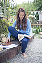 Woman sitting on a bench in the garden reading a book - OPF000078
