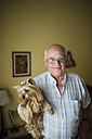 Portrait of smiling senior man  holding his Yorkshire Terrier - RAEF000454