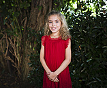 Portrait of a smiling little girl wearing a red dress - RAEF000433