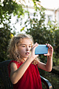 Little girl wearing red dress taking a picture with smartphone - RAEF000455