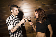 Couple toasting with red wine in front of a wooden wall - JASF000063